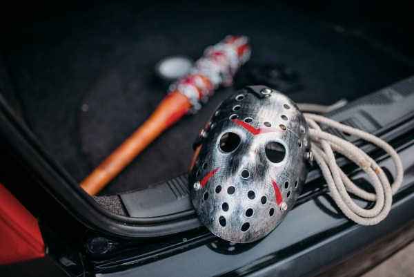 Hockey mask, baseball bat wrapped with bloody metal chain, duct tape and rope closeup, serial murderer concept. Psycho man instruments in opened car trunk, maniac.