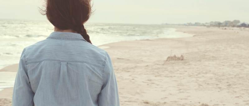 mulher de costas junto ao mar em numa pose pensativa