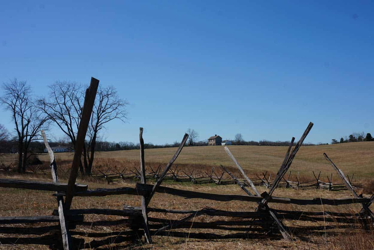 wood split-rail fences in the foreground and Henry House at Manassas in the distance