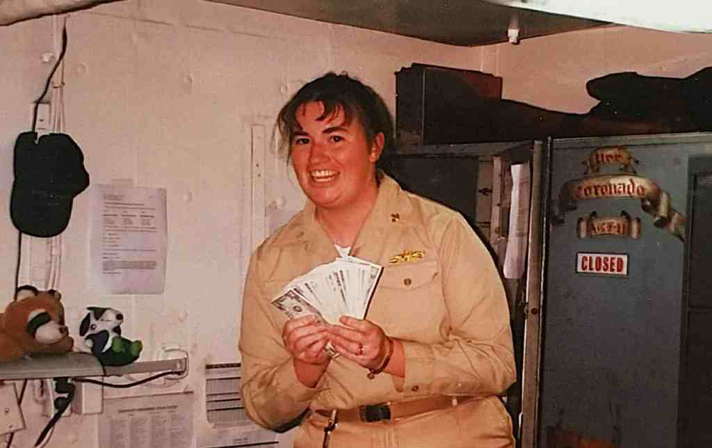 disburing officer holds money outside open safe onboard uss coronado AGF-11