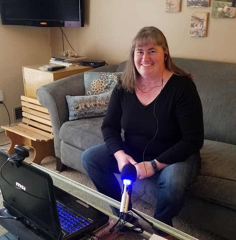woman sitting on couch with computer and microphone in front of her