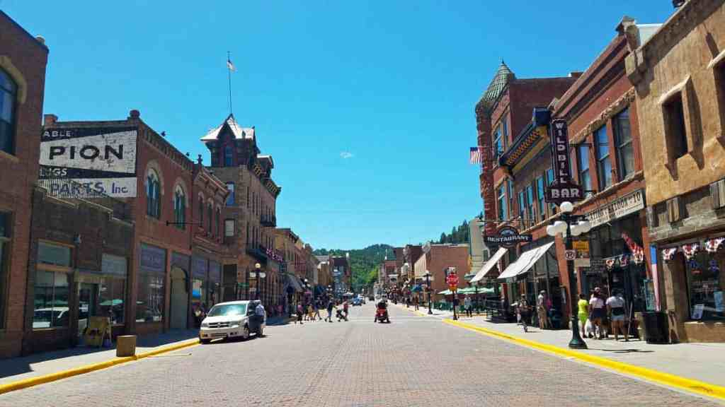 Standing in the middle of the road looking down the street through the historic Deadwood, SD main street area.