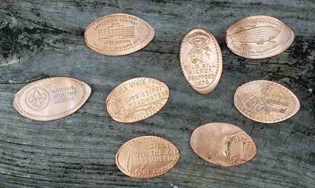 a collection of squashed pennies on a table including pennies from Billy the Kid Museum and the National Scouting Museum