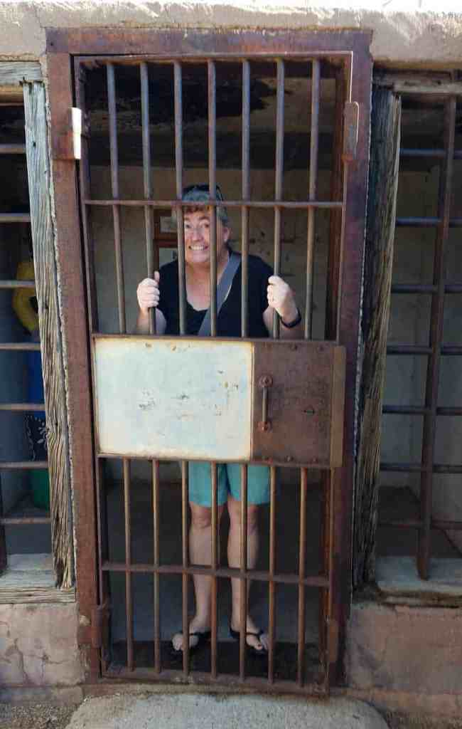 person posing for photo inside an old jail cell