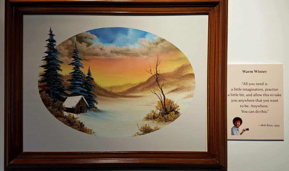 Bob Ross painting entitled Warm Winter features a cabin next to a meadow and trees with an orange glowing sky