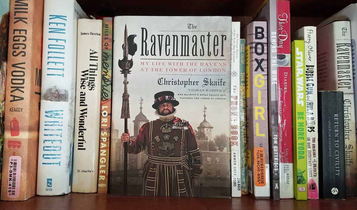 Cover of Ravenmaster: My Life with the Ravens at the Tower of London by Christopher Skaife displayed on a bookshelf with various other titles