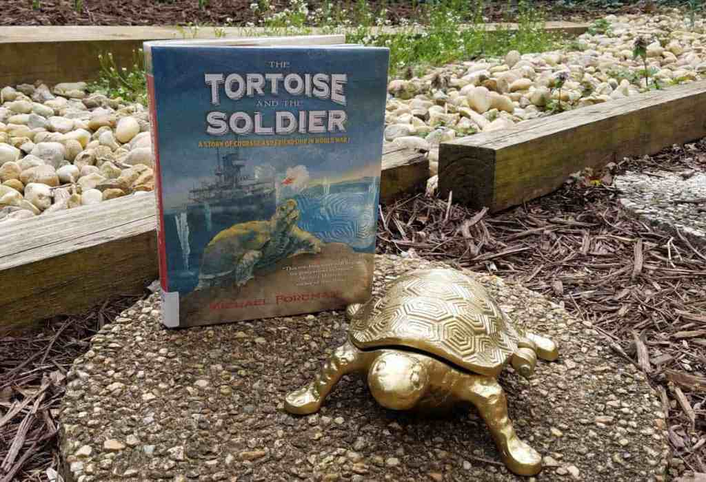 Cover of The Tortoise and the Soldier shown next to a small golden turtle sculpture