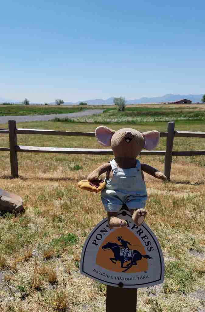 vacation mouse travel mascot sitting on top of a pony express historic trail marker sign looking over the former site of Camp Floyd Utah