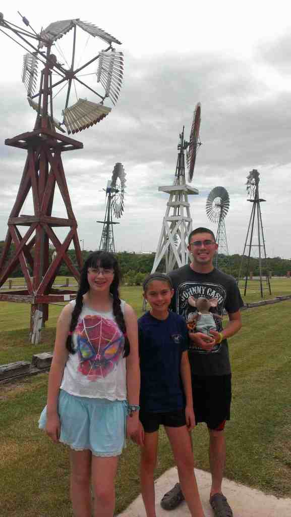 3 children standing near several windmills on display outside the American Windmill Museums