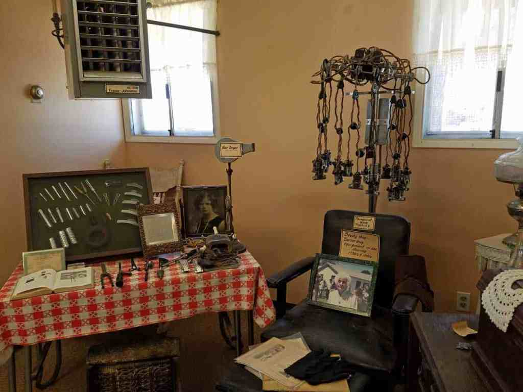 museum display of beauty salon tools and chair including hanging electric curling rods