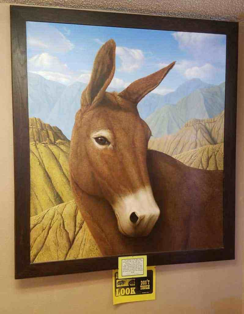 Lifelike painting of a mule against a backdrop of tan desert hills