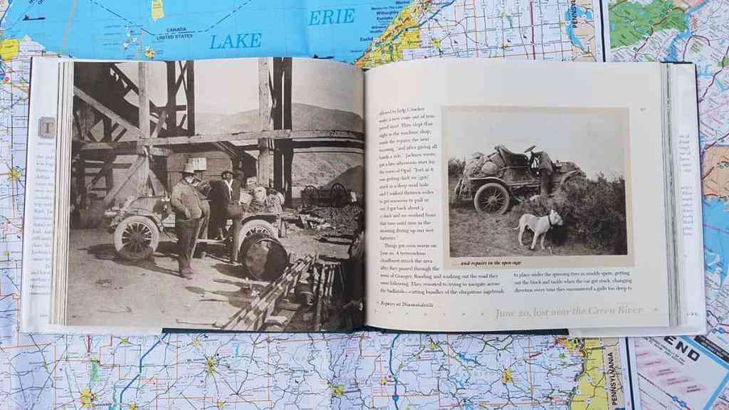 Open book on top of road map. Picture is sepia tone image of a 1903 car under a railroad trestle. Facing page has text and photo of car under repair with dog standing nearby