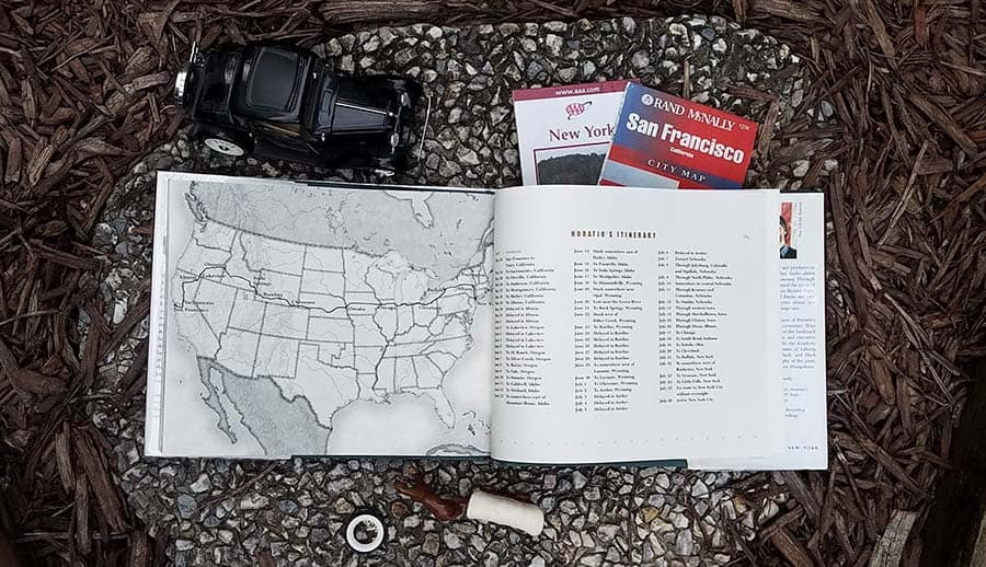 open book displaying a map of the united states showing a route from California to New York. On the facing page, a day by day itinerary of the cross-country journey