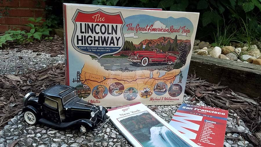 front cover of book titled The Lincoln Highway displayed with paper road maps and an old model car