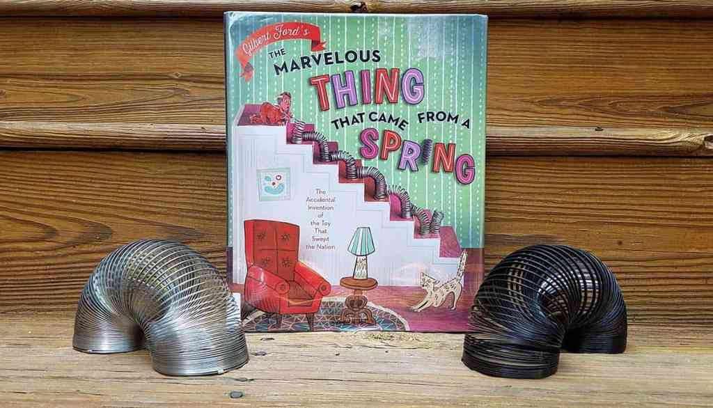 Book cover The Marvelous Thing That Came From a Spring displayed with two slinky toys - one on each side - in an arch