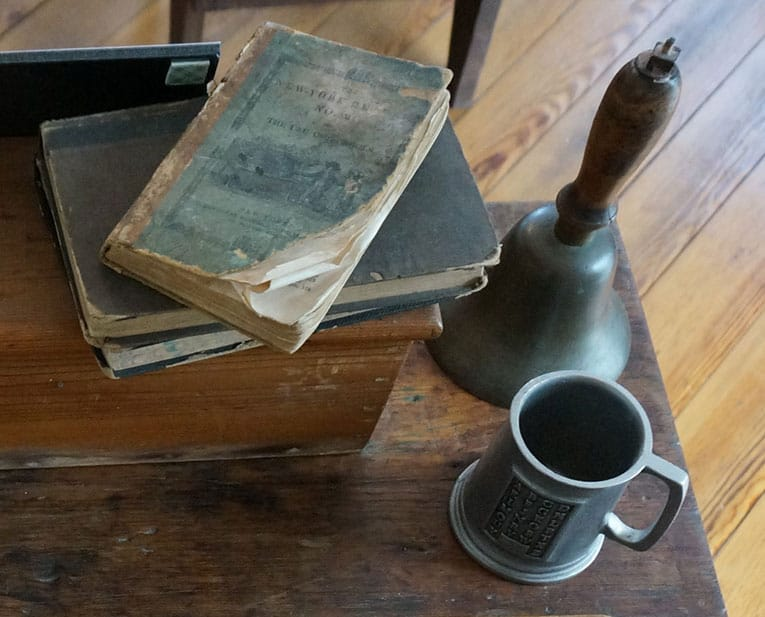 books, pewter mug, and bell on desk from post Civil War classroom