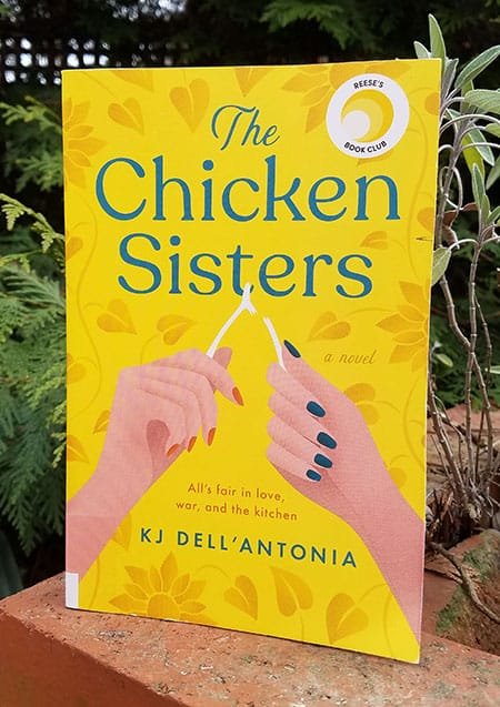 The Chicken Sisters book cover, yellow background with two hands pulling the wishbone