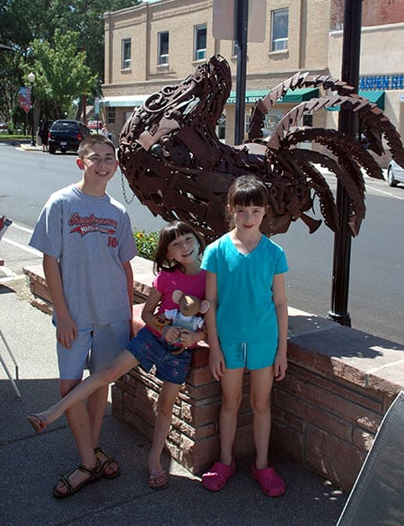 three children stand in front of headless chicken statue made from recycled metal parts