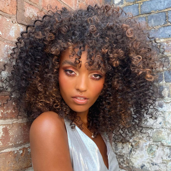 fall 2021 hair color trends warm caramel curly hair brunette