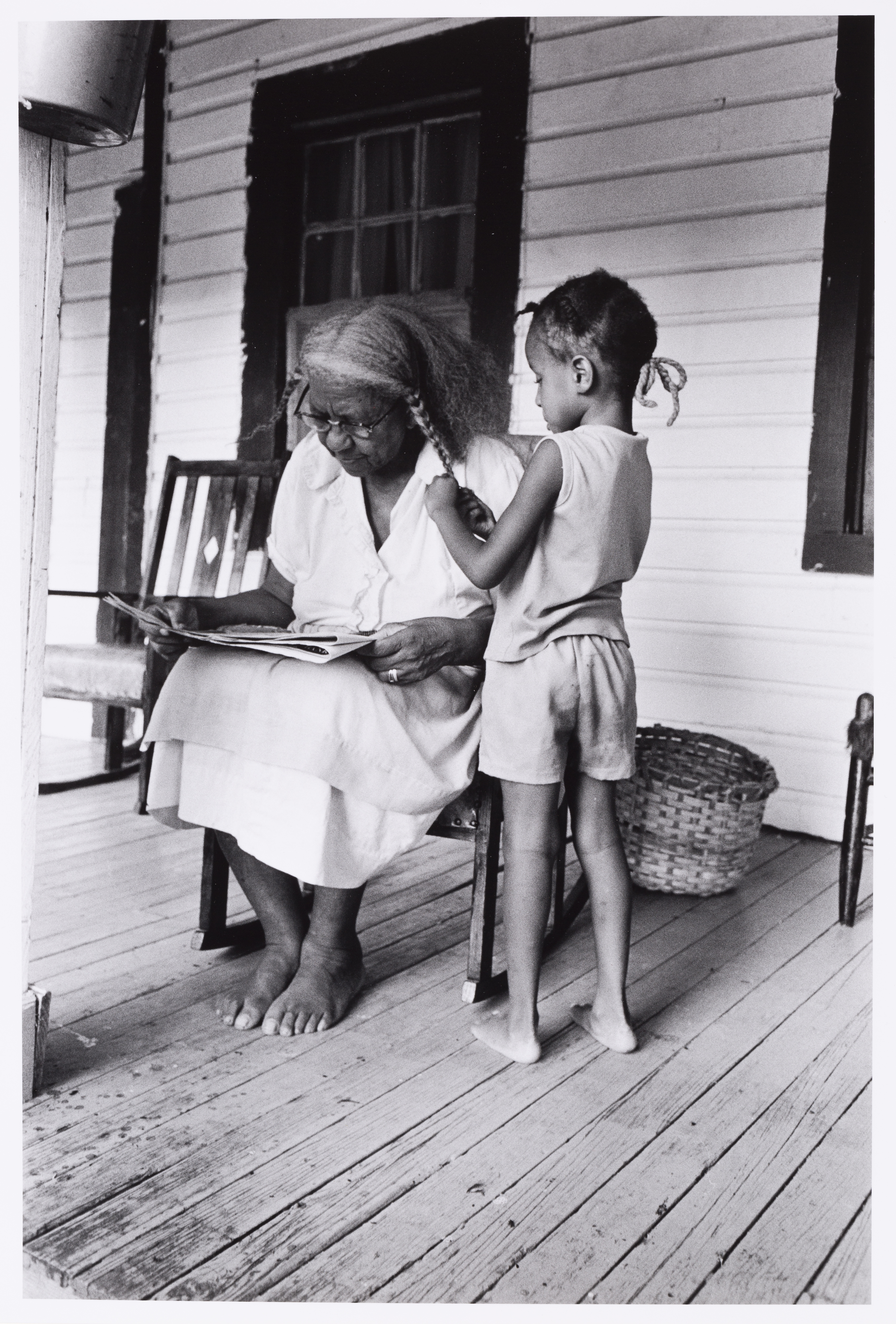 Older dark-skinned woman reading in a rocking chair on a porch while a child braids her hair