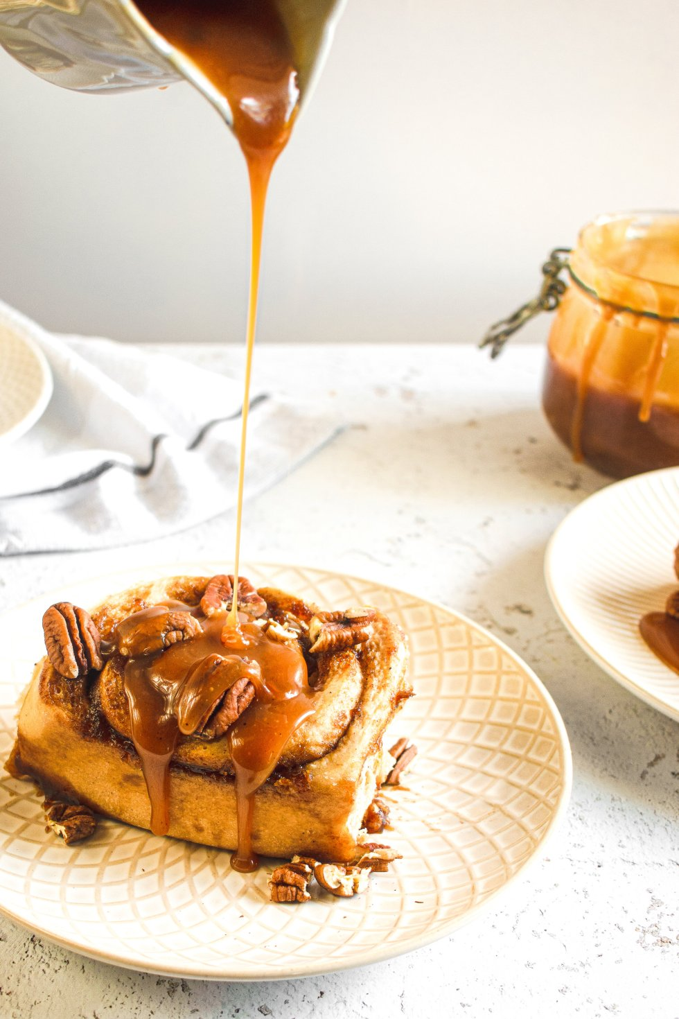 Apple butter cinnamon roll with apple cider caramel being drizzled on top