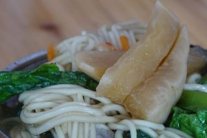 Close up of vegetarian noodle soup topped with taro