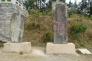 Two slabs sticking out of the ground with inscriptions of them