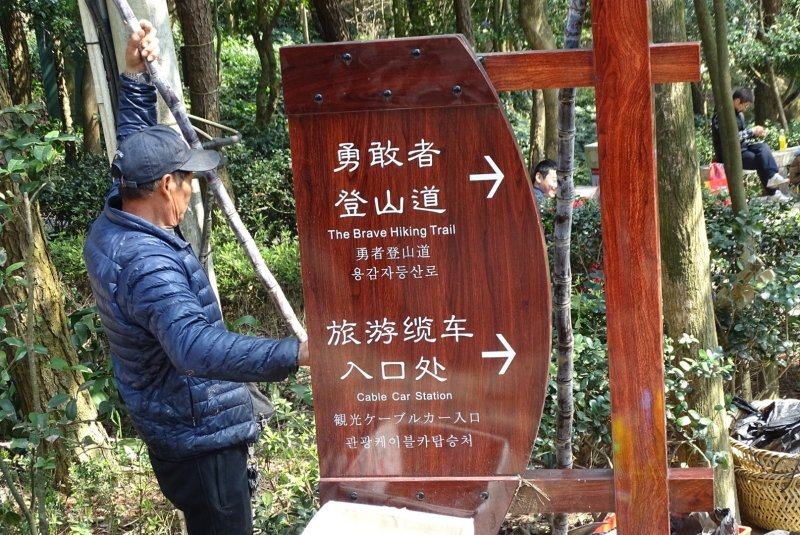 Wooden sign with arrows to the right pointing towards the Brave Hiking Trail and Cable Car Station, in both English and Chinese