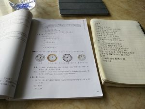 A Chinese course book and a notebook with Chinese writing