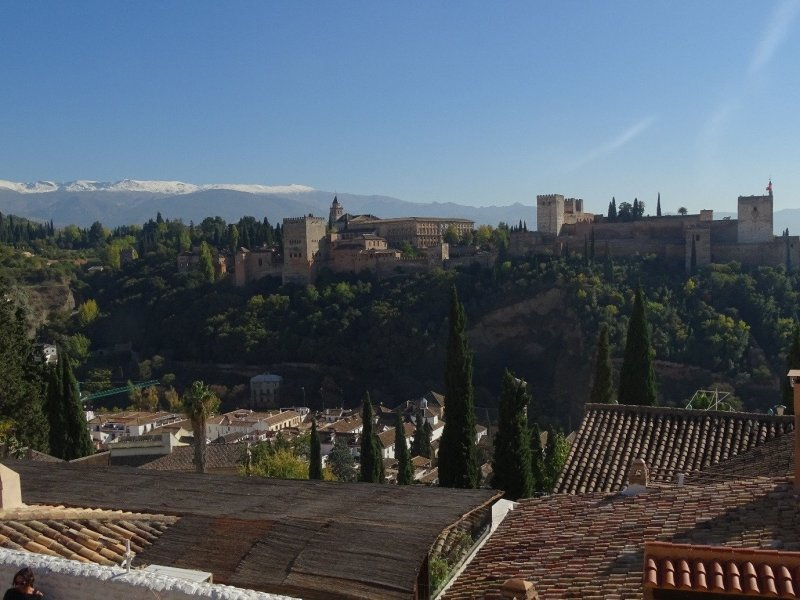 A view from Mirador San Nicolas showing some rooftops and the Alhambra. Snowy peaks of the Sierra Nevada behind.