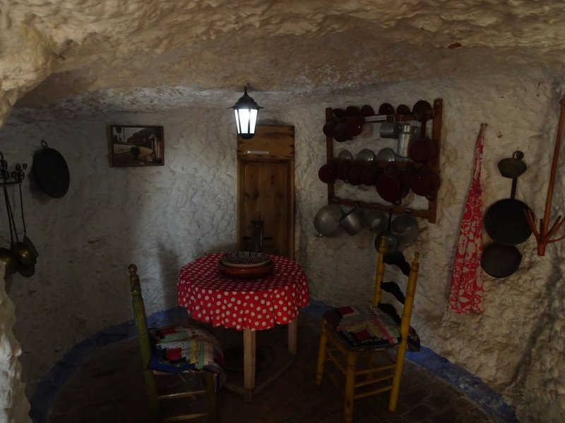 A kitchen inside the Sacromonte Caves Museum with a round table and two chairs