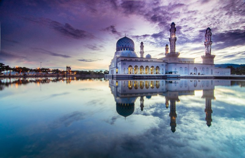 Kota Kinabalu mosque looking out over waterfront at twilight, reflections long on the water