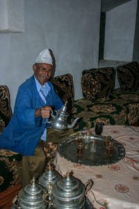 Old Moroccan man pouring out some mint tea into shot glasses on a silver tray