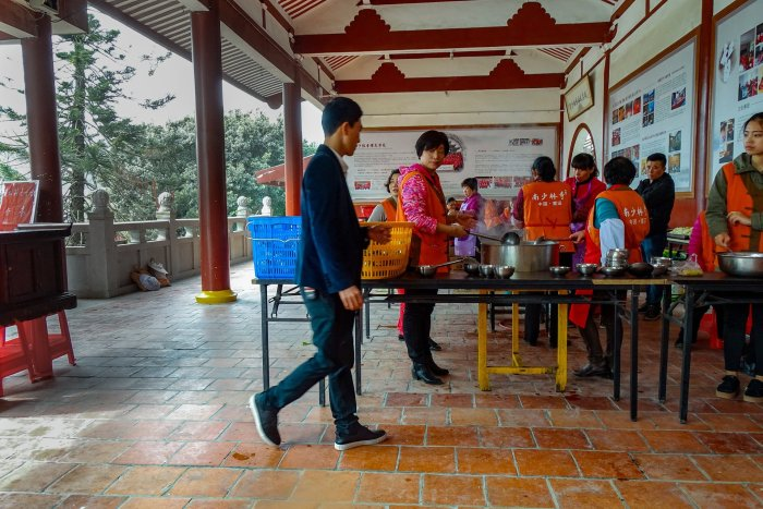 A temple kitchen with community members in orange jackets preparing food.
