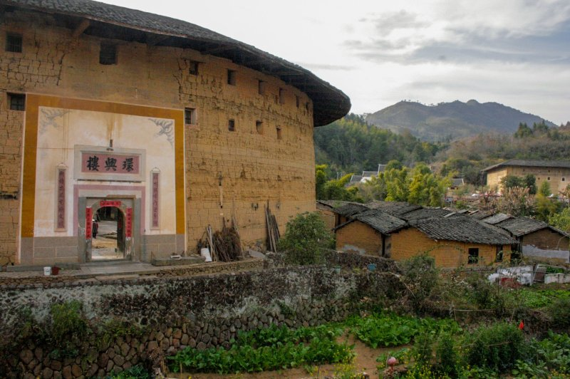 Front view of Zhengchenglou Fujian Tulou.  The tulou is on the left while the village and some hills are in the background.