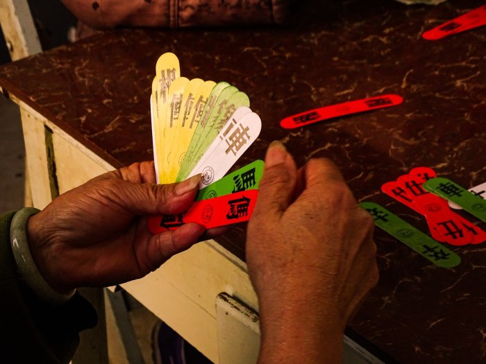 The hands of an elderly Chinese woman with long and thing cards in her left hand that are yellow, green, white and red, Chinese symbols upon the cards.