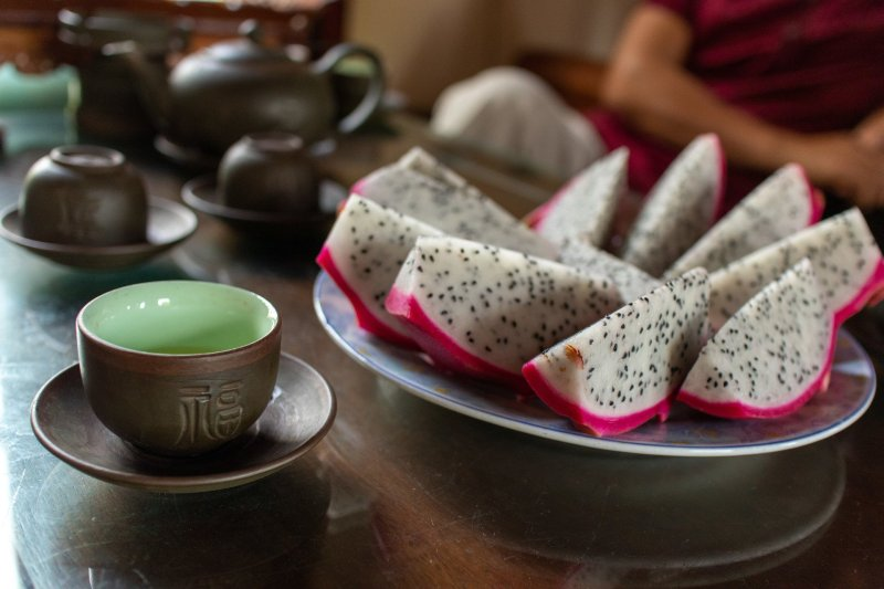 Dragonfruit and tea upon a wooden table, Asian style teacups.