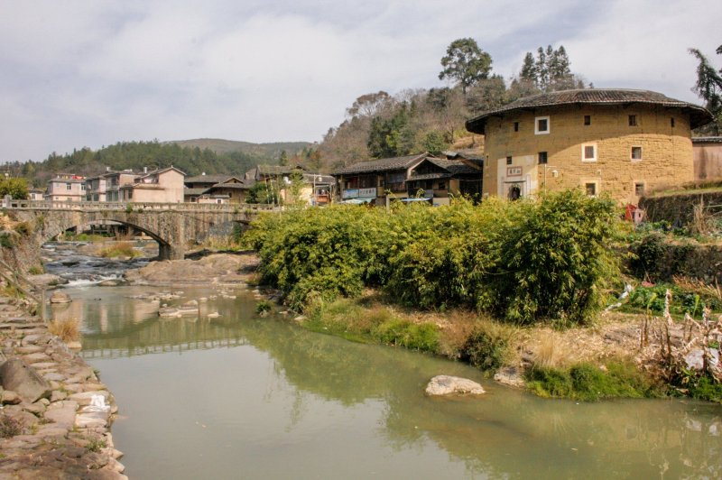 View of Hongkeng village across a river. Tulou on right, village and bridge in background.