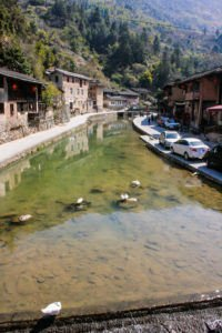 View of the brook, some cars and traditional houses in Taxia village.