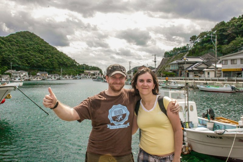 Chris (left) and Ola (right) in a marina on Tsushima Island, Japan. Grey clouds in the distance and lots of boats.
