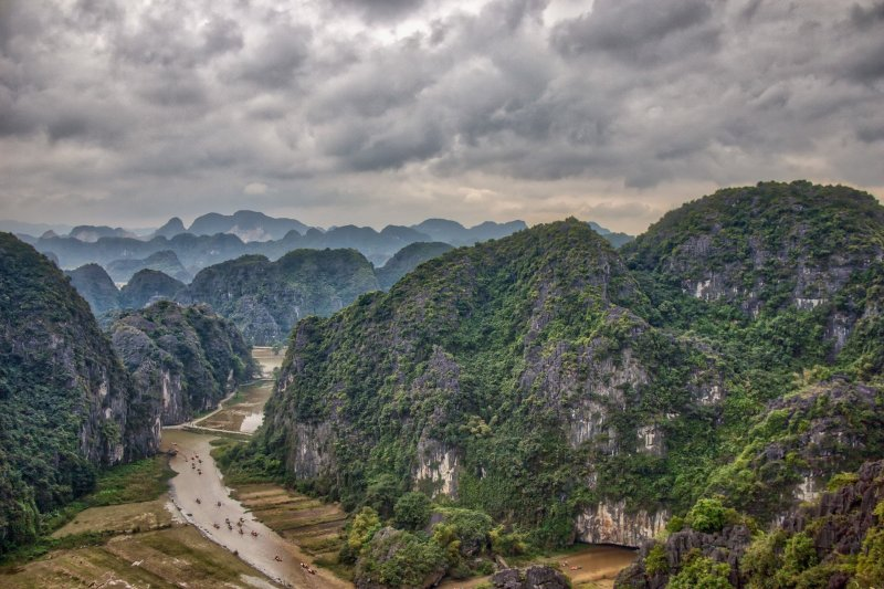 A scenic view from Hang Mua viewpoint with a stormy sky. Tam Coc river is running through the rice paddies in the valley, and tourist boats are sitting on top of this.