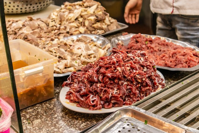 Large trays of raw beef and chicken on a restaurant kitchen's table