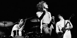 """Singer Roger Daltrey of the Who twirls his hand microphone by its cord during the final performance of the rock opera """"Tommy,"""" at the Metropolitan Opera House in New York, June 7, 1970.  Drummer Keith Moon and lead guitarist Pete Townshend, who wrote """"Tommy"""" perform in the background.  (AP Photo/Harry Harris)"""