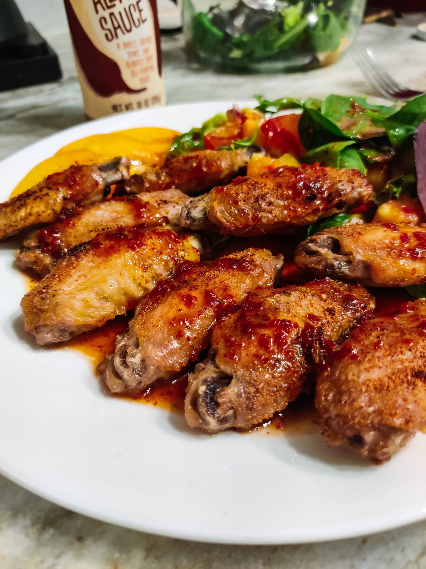 A white plate on a marble countertop with crispy chicken wings and salad drenched in Trader Joe's Honey Aleppo Sauce. Part of the sauce bottle and a big clear, glass bowl of salad are visible in the background.