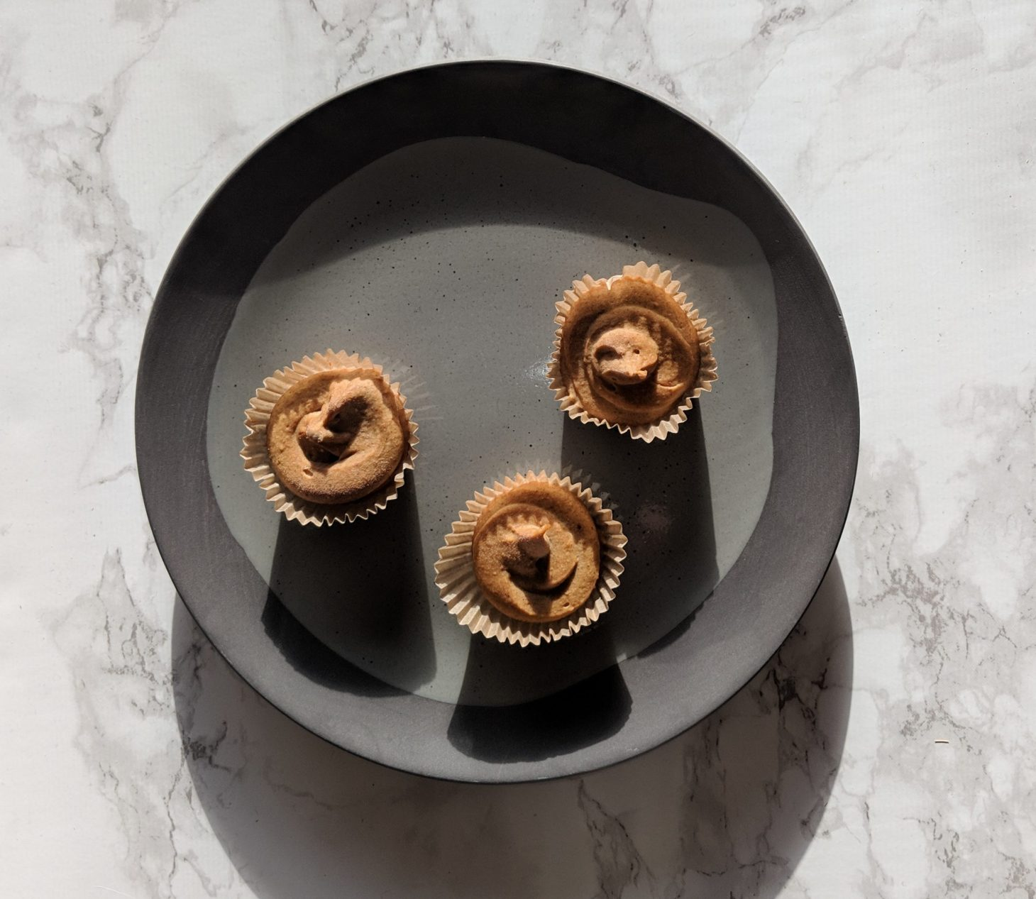 An overhead shot of a gray textured plate featuring three mini pumpkin cheesecake bites on a white marble background. The light is coming from the top of the image so there is a shadow underneath each of the three mini cheesecakes.