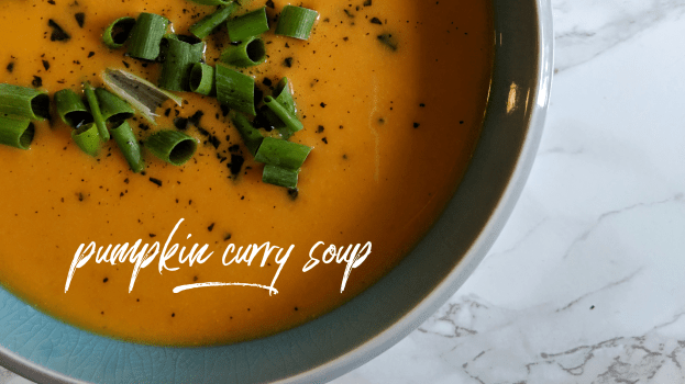 """An overhead shot of pumpkin curry soup in a blue and gray bowl with scallions and black salt. The bowl is on a white marble background. There is thin white cursive text over the soup that reads """"Pumpkin Curry Soup"""""""