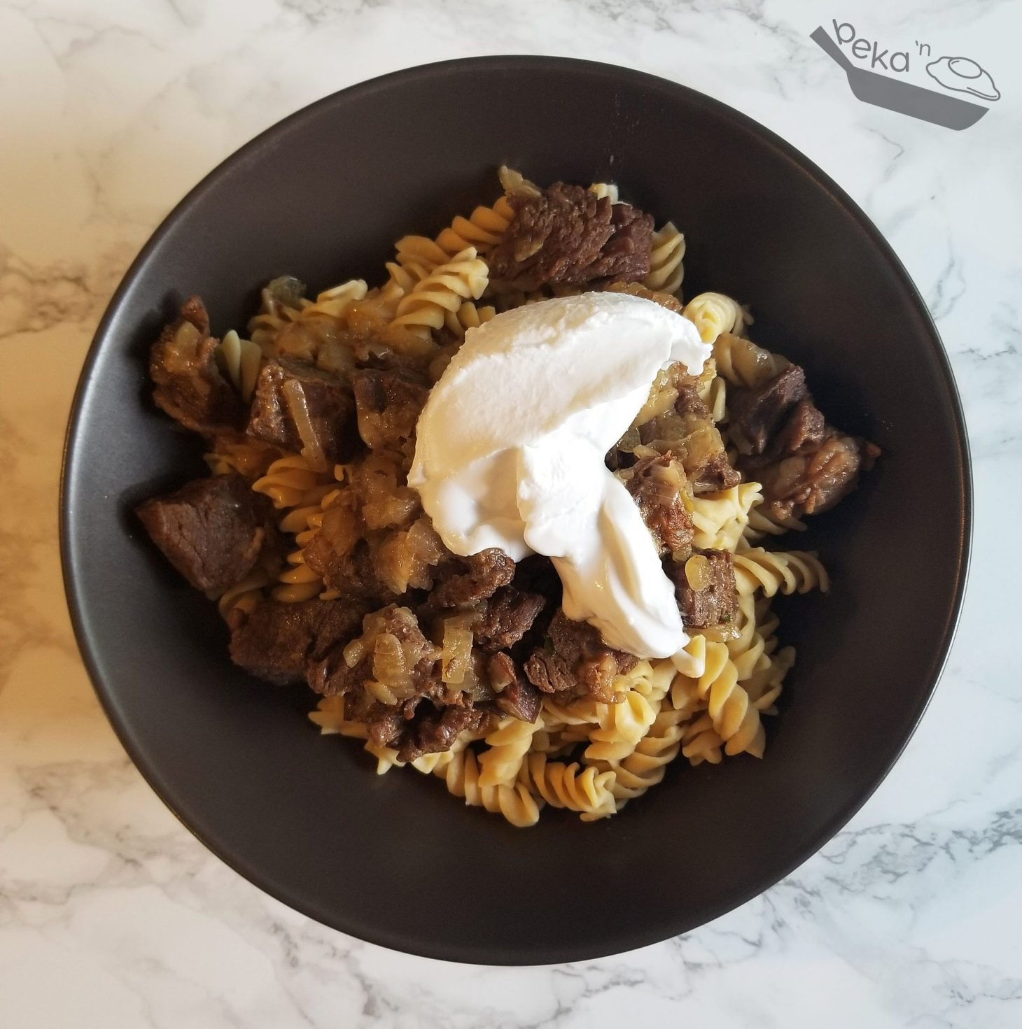 An overhead shot of my homemade beef stroganoff in a brown ceramic bowl on a white marble background. In the bowl is also coconut milk yogurt and red lentil pasta, but it has not yet been mixed together.
