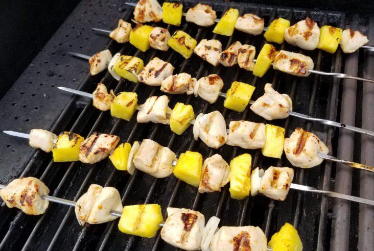 Chicken, pineapple, and onion pieces on long metal skewers on an outdoor grill. The skewers are laying perpendicular to the grill grates.