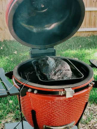 A photo of our big red grill with the lid up and a large brisket inside. You can see grass and part of our backyard fence in the background.