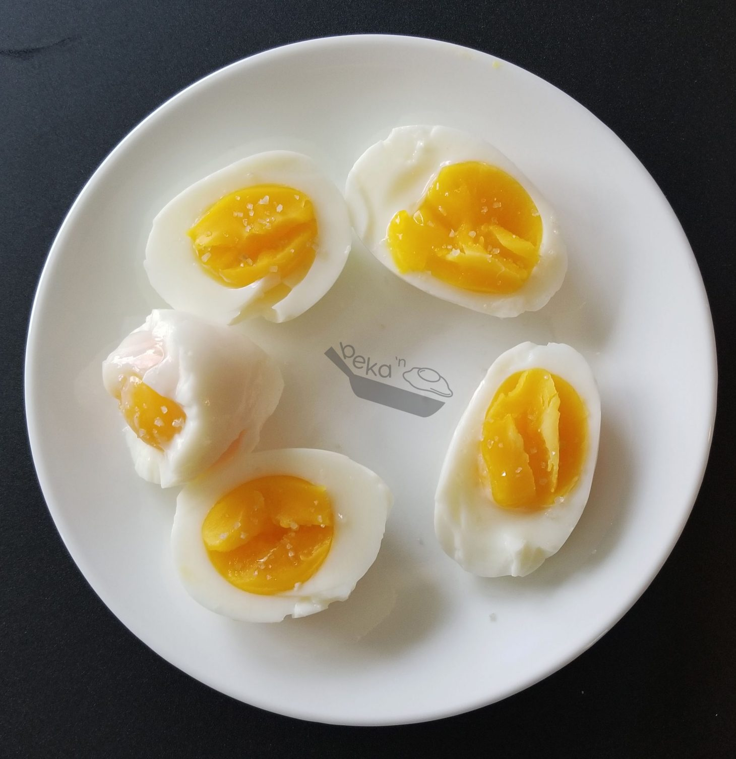 An overhead image of five sous-vide egg halves on a white plate. Black background.